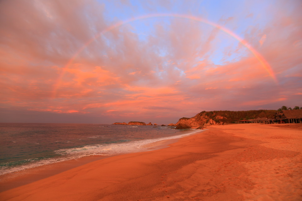 Sunrise over the beach with a rainbow.