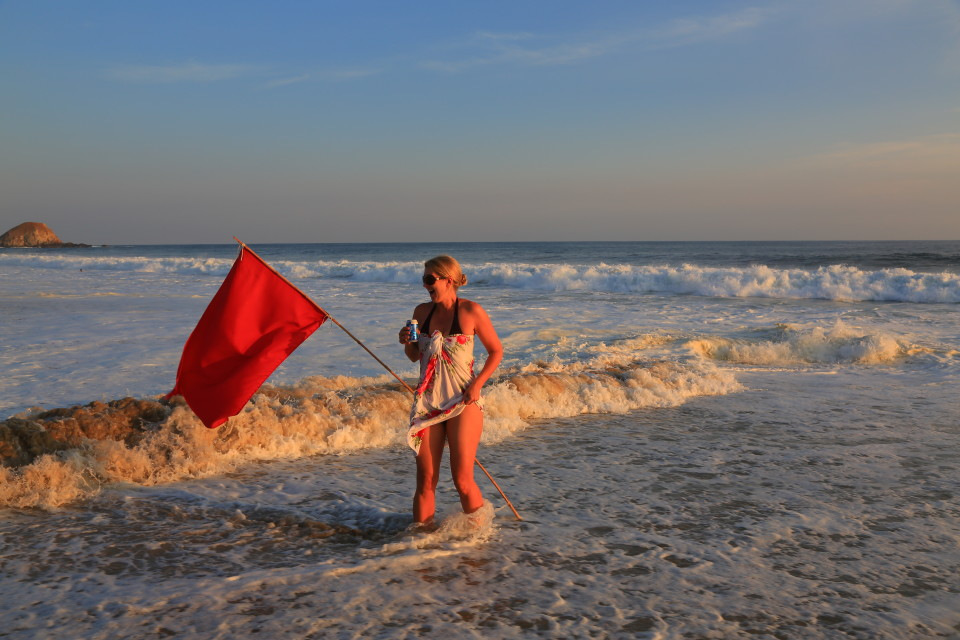 I love this picture. I was posing next to the red flag for the surf condition when a wave crashed into me and almost took me and my cold beer out. Those waves are no joke.