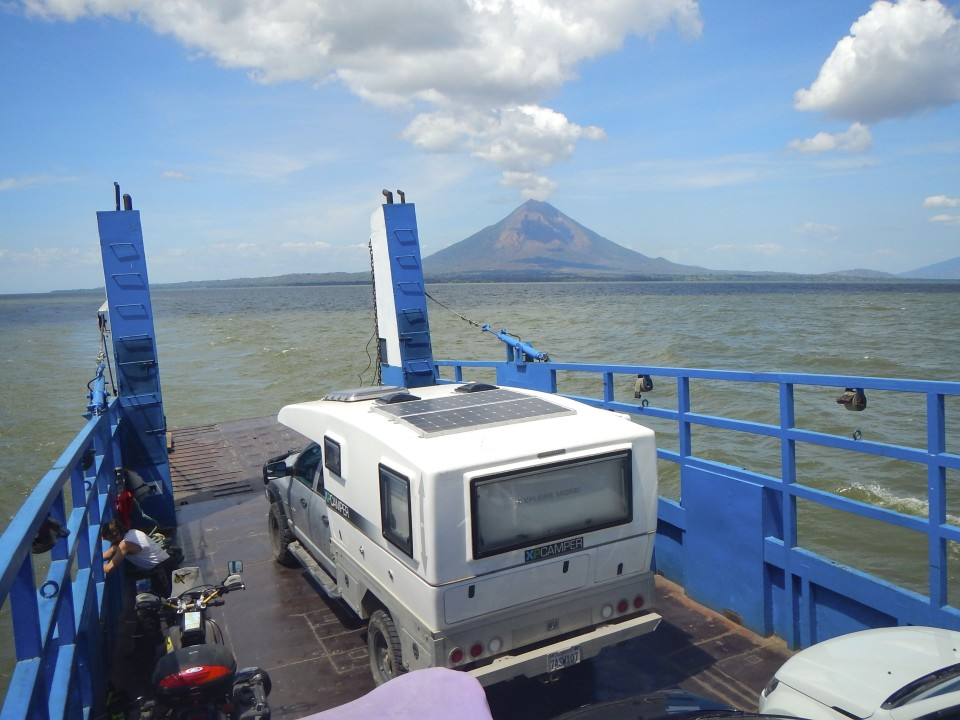 On the ferry to the island with one of the two volcanoes looming in the background.