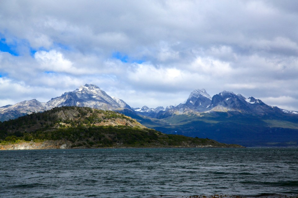 The snowy mountains across the water.